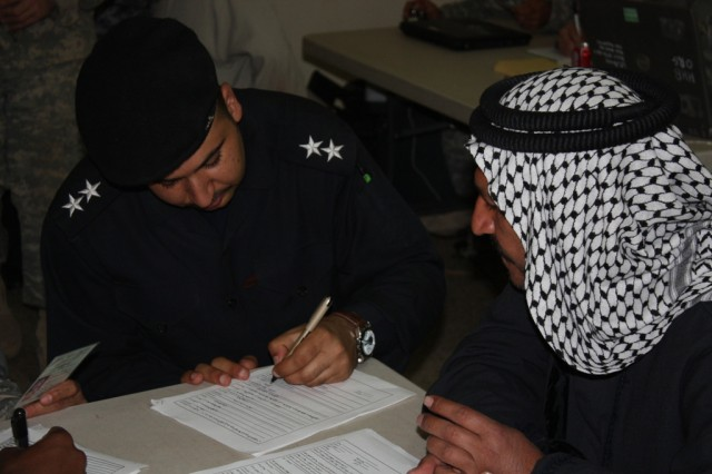 CONTINGENCY OPERATING BASE SPEICHER, TIKRIT, Iraq - First Lt. Ra'ad Sami Muhamed, a shift leader at the Tikrit Police District Headquarters, interviews a man from the town of Owja, a small community outside Tikrit. Following the interview, the men who came to reconcile were seen by a committee which reviewed their files to determine their eligibility for reconciliation based on Iraqi law.