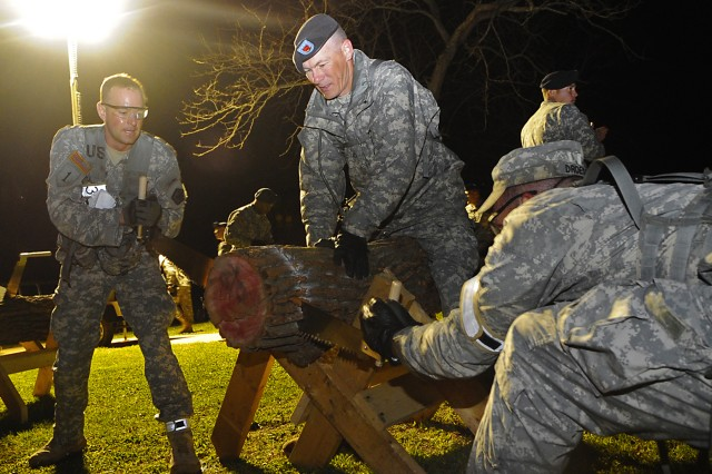 """Competitors are under the gun to cut a log a carry it to a designated spot during the final phase of the 52-hour long """"Best Sapper"""" competition at Fort Leonard Wood, Mo."""