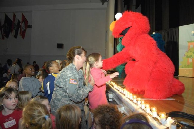 Elmo greets a Soldier and her daughter at the Talk, Listen, Connect live show at Ft. Dix, NJ on Oct. 24, 2008.  The 60-minute live performances were sponsored by Sesame Workshop, the nonprofit organization behind Sesame Street, and the USO.