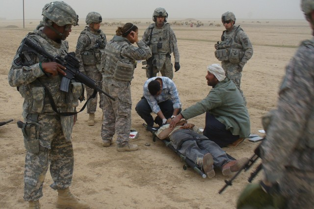 A passing Iraqi doctor (center) and an Iraqi sheppard administer aid to an injured Iraqi motorist following a vehicle collision near Tikrit, Iraq. Soldiers with the 607th Military Police Battalion, 8th Military Police Brigade assisted the Iraqi doctor and Iraqi Police with the safety of the incident site and the transition of the motorists to a hospital in Tikrit.