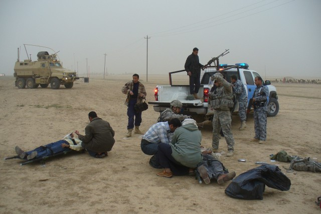 A passing Iraqi doctor (center) and an Iraqi sheppard administer aid to an injured Iraqi motorist following a vehicle collision near Tikrit, Iraq. Soldiers with the 607th Military Police Battalion, 8th Military Police Brigade, assisted the Iraqi doctor and Iraqi Police with the safety of the incident site and the transition of the motorists to a hospital in Tikrit.