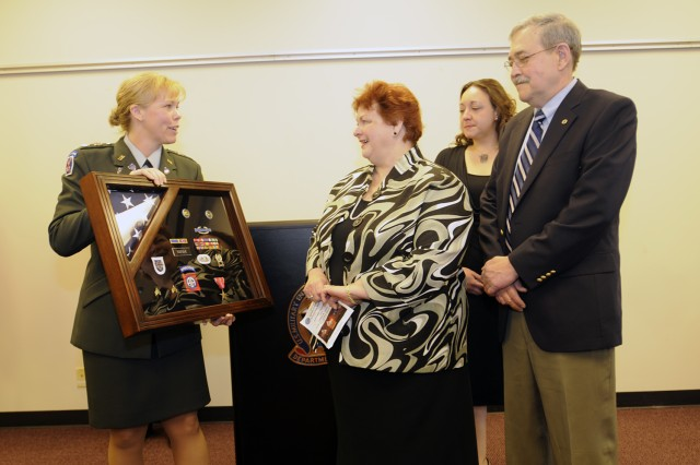 Lt. Col. Holly Gay (left), commander of the Chicago Military Entrance Processing Station, presents a shadow box to the parents and sister of Sgt. Joe Vanek during a ceremony to mark the dedication of the Joseph M. Vanek Room at the Chicago MEPS. The room - where new recruits swear their oath of allegiance upon entering the military - was re-named in Sgt. Vanek's honor during a ceremony April 20, attended by family, friends, and members of Vanek's old unit, Company C, 2nd Battalion, 325th Airborne Infantry Regiment, 82nd Airborne Division. Sgt. Vanek, an infantry squad leader, was killed in Iraq in 2007.