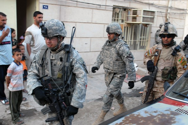 1st Lt. Mark Reinke (left), C Company, 2nd Battalion, 5th Cavalry Regiment, followed by an interpreter and an Iraqi Army Soldier, patrol a neighborhood in Sadr City, April 19.