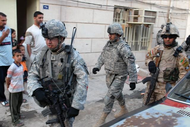1st Lt. Mark Reinke (left), C Company, 2nd Battalion, 5th Cavalry Regiment, followed by an interpreter and an Iraqi Army Soldier, patrol a neighborhood in Sadr City, April 19.