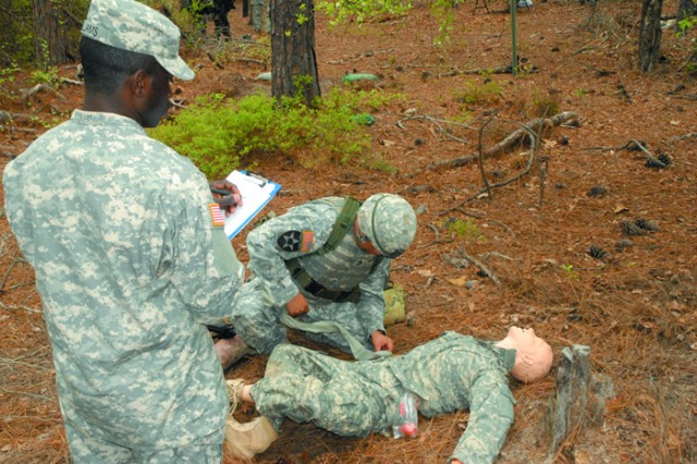 Sgt. 1st Class Ryan Whitebull, 1st Battalion, 61st Infantry Regiment, kneeling, demonstrates how to apply a tourniqute as an evaluater grades him.