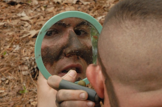 Sgt. 1st Class George Simmons, 2nd Battalion, 60th Infantry Regiment, applies camouflage to his face Monday during the Drill Sergeant of the Year competition. Competitors were timed on how fast they could camouflage themselves and judged on how effective their efforts were.