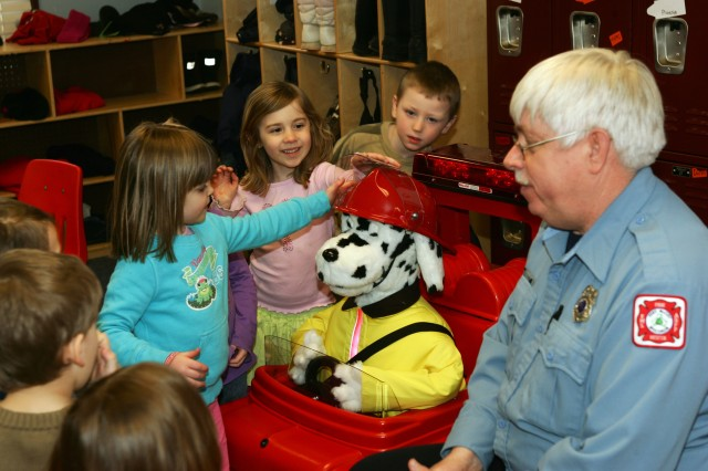 Curt Ladwig of the Fort McCoy Fire Department and Patches the Fire Dog, and Pumper, the fire engine, talk about Fire Safety with children at Fort McCoy.