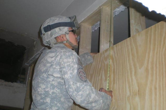 BAGHDAD - Sgt. Jinjian Tan, construction team leader, Company A, 46th Engineer Combat Battalion (Heavy), a Canton, China native, installs plywood, April 4.  Tan and his team of engineers are making numerous upgrades to a high-rise building that will be used to house Coalition Soldiers.
