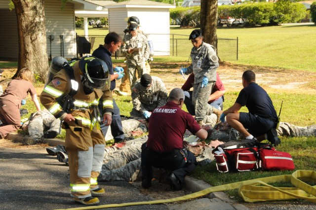 """Fort Rucker first responders tend to casualties following a mock terrorist bombing in one of the post housing areas April 23. The simulated incident was part of a command Force Protection Exercise conducted to test official emergency procedures."""""""