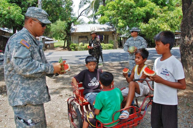 "Fort Magsaysay, Philippines - Staff Sgt. Dennis Calvo, a Soldier assigned to 1st Battalion, 294th Infantry Regiment, Guam National Guard, shares watermelon with children during a community relations project near Fort Magsaysay during Balikatan 2009.  Balikatan, which is Tagalog for ""shoulder to shoulder,"" is an annual exercise which brings together the militaries from the US and the Republic of the Philippines to ensure military readiness and interoperability in the event of a natural disaster and to provide humanitarian relief needs."
