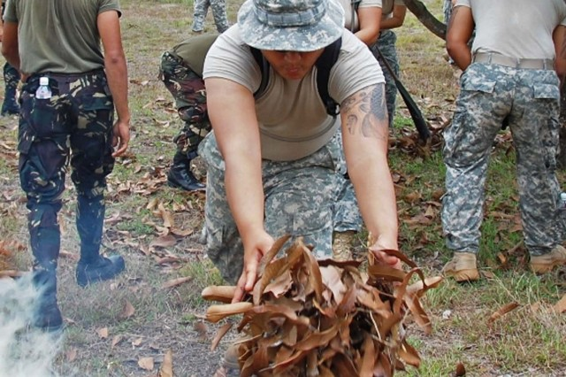 "Fort Magsaysay, Philippines - Soldier assigned to 1st Battalion, 294th Infantry Regiment, Guam National Guard, along with Republic of the Philippine Army soldiers assigned to the 49th Infantry Battalion clear leaves and debris during a community relations project near Fort Magsaysay during Balikatan 2009.  Balikatan, which is tagalog for ""shoulder to shoulder"" is an annual exercise which brings together the militaries from the US and the Republic of the Philippines to ensure military readiness and interoperability in the event of a natural disaster and to provide humanitarian relief needs. This is the 25th year the RP has hosted the month-long exercise."