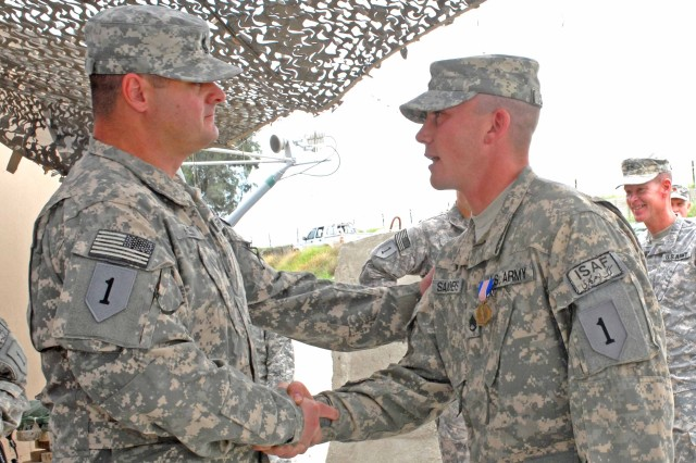 1st Sgt. Michael Klein of Headquarters Company, 3rd Brigade Combat Team, 1st Infantry Division, congratulates Staff Sgt. Kevin Sanders, Soldiers Medal recipient for his achievement. The award ceremony was held April 14 at Forward Operating Base Fenty in Afghanistan.