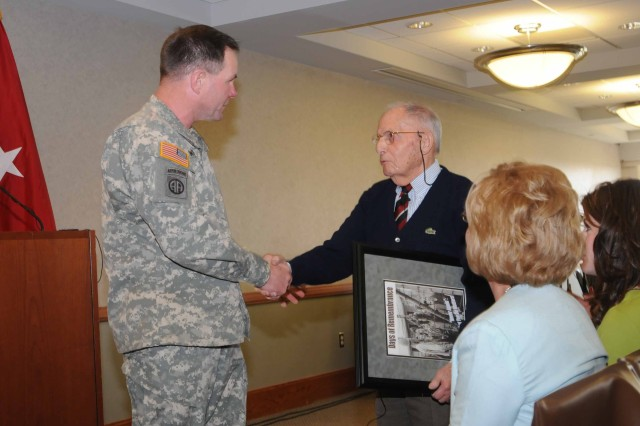 Brig. Gen. Perry Wiggins, 1st Inf. Div. assistant division commander for maneuver, presented a framed poster of the event to Robert Behr following the Holocaust survivor's Days of Remembrance Observance presentation April 15 at Riley's Conference Center.