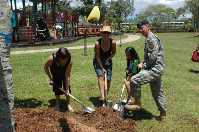SCHOFIELD BARRACKS, Hawaii - Earth is unmoved to symbolize a tree planting at the Earthday Festival, April 19. Pictured (from left to right) is Jacqueline Ralya, with the Kaulunani Urban & Community Forestry Program; Claire Ridding-Johnston, Army Hawaii Family Housing project director; Amber Mirafuentes, 10, a fifth grader at Mililani Mauka and winner of the Arbor Day poster contest; and Col. Matthew Margotta, commander, U.S. Army Garrison-Hawaii.