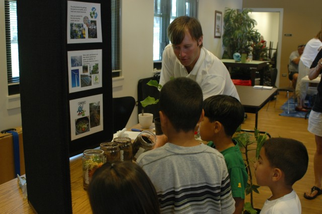 SCHOFIELD BARRACKS, Hawaii - Mike Poteet engages children at the Hawaii Agriculture Research Center exhibit during the Earthday Festival at the Kalakaua Community Center, April 19. Poteet explained why compost is so important to the aina, or land.