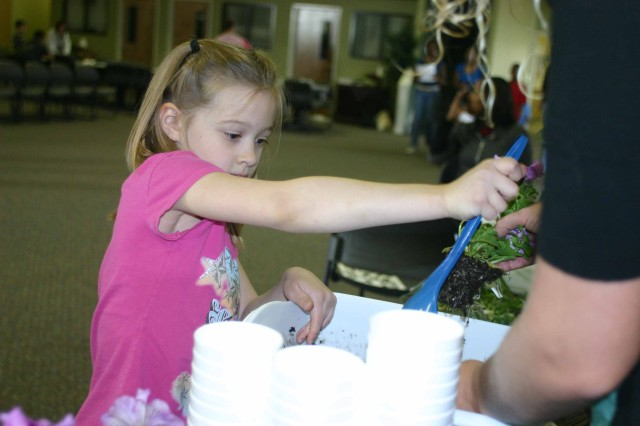 Abby, 7, daughter of Bob Clifton, Youth Parent Support, Army Community Services, plants a May Day flower at the K-State Extension booth at the Spring Fling April 18 at Army Community Service. Abby and many others who planted flowers also were able to name them.