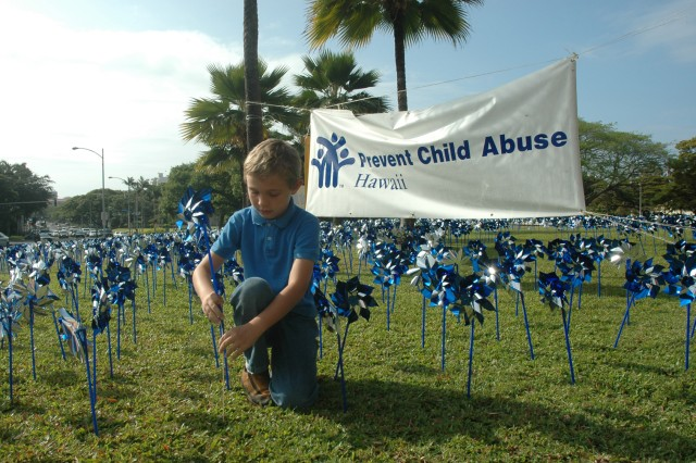 HONOLULU - Eli Jorr, 8, places a pinwheel on the Capital lawn, April 20, to draw attention to child abuse and neglect. Community volunteers along with Prevent Child Abuse Hawaii and the Child Abuse Prevention Planning Council placed more than 5,000 pinwheels on the lawn to raise awareness. The pinwheels will be on display through April 26.