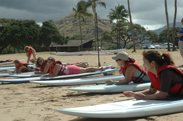 WAIANAE, Hawaii - Family members practice techniques on Pokai Beach before attempting to paddle on the stand up board in the water. Blue Star Card holders enjoyed an introduction to the art of stand up paddling with a combined effort from FMWR and Outdoor Recreation, April 16.