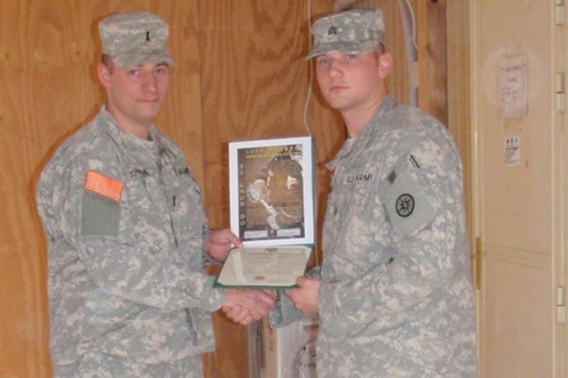 Sgt. Gregory Beerli, from Baltimore, Md., receives his promotion certificate from 1st Lt.  Floyd Jordan, an Etters, Pa. native at Camp Stryker, Iraq. Both Soldiers are deployed with the 3rd Detachment, 374th Financial Management Company, 10th Sustainment Brigade in support of Multi-National Division - Baghdad.