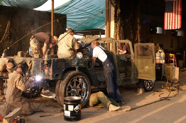 "Jesse James (center, w/coveralls) watches as service members work on a hybrid humvee at the ""Skunk Werks"" welding shop at Logistical Support Area Anaconda, Iraq, December 2005. The mechanics were challenged to create a unique humvee for the popular Discovery Channel show, Monster Garage."