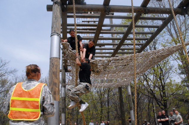 In fear of being disqualified, members from the first place women's team help pull their last teammate up the rope on the tough one, the second of the five events on the obstacle course. The obstacle course challenge was the first annual competition held at the Camp Hovey obstacle course, April 18.
