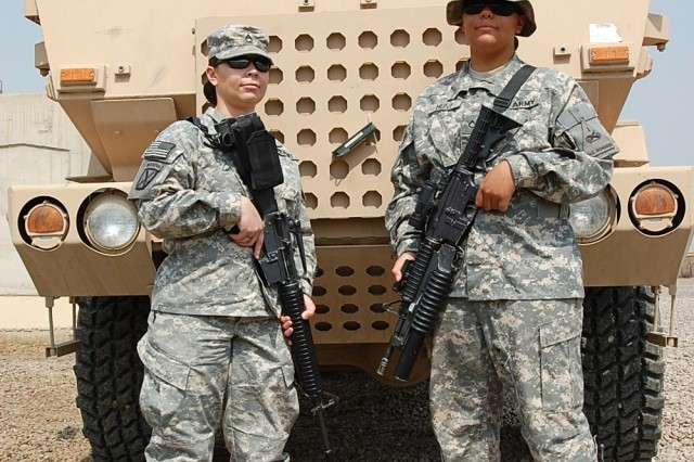 Staff Sgt. Melodie A. Hunt (pictured left) and her sister Pfc. Mallorie A. Hunt, Lumberton, N.C. natives, stand in front of a Military Tactical Vehicle. The Hunt sisters are currently deployed to Baghdad, Iraq as a part of the 449th Theater Aviation Brigade out of Morrisville, N.C. and 47th Forward Support Battalion out of Baumholder, Germany.