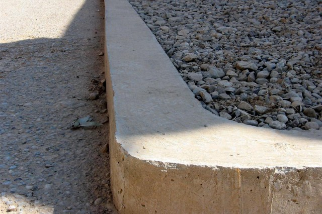 """California Guardsmen from Bravo Company, 1st Battalion, 184th Infantry Regiment, 30th Combat Sustainment Support Battalion, 16th Sustainment Brigade, made noticeable improvements to their company area at Contingency Operating Base Q-West, Iraq, April 10, to include replacing sandbags with a concrete curb, adding a pull-up bar, packing away old parts, beautifying the area and creating parking spots. Guardsmen also painted the """"Bushmaster"""" company logo onto the large barrier wall near the entrance to the company area."""