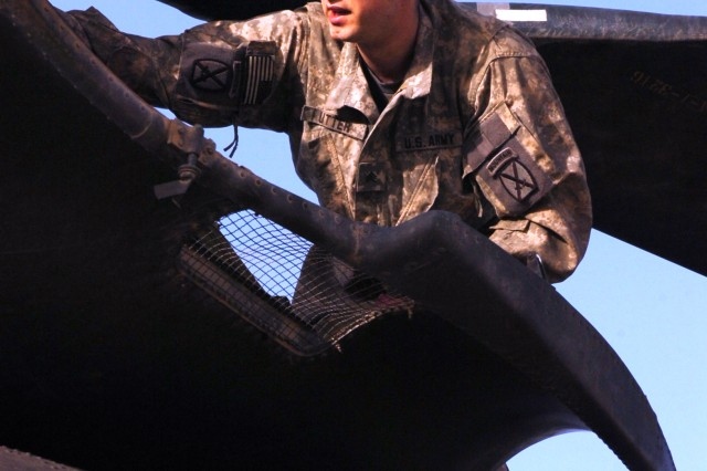 Sgt. Chris Utter, a Reedsburg, Wis. and flight engineer with B. Company, 3rd General Support Aviation Battalion, 10th Combat Aviation Brigade, 10th Mountain Division, adjusts the rotors atop a CH-47 Chinook Helicopter, at Contingency Operating Base Speicher, near Tikrit, Iraq, April 22. (U.S. Army photo by Pfc. Jesus J. Aranda, Task Force Lightning Public Affairs)