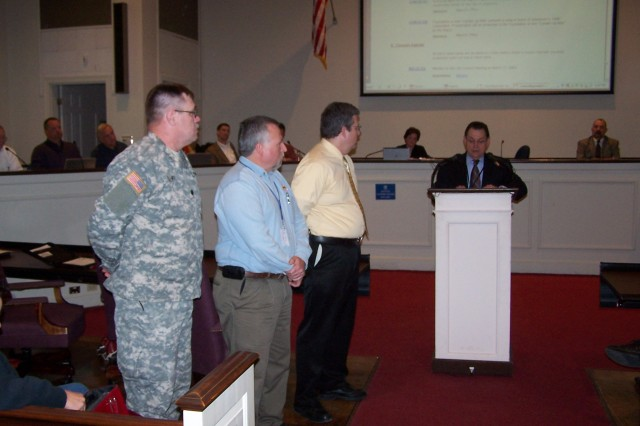 "Lieutenant Colonel Dale Deehr, Mr. Jeff Presley, and Mark Salcedo listen as Mayor Harold Perrin reads a proclamation awarding the ""Key to the City"" of Jonesboro, Arkansas to the Armed Services Blood Program."