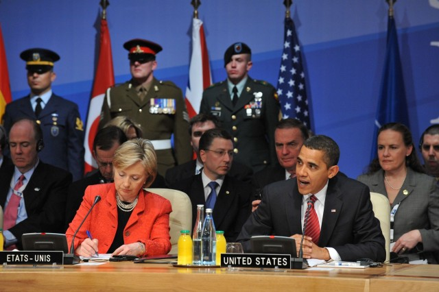 Sgt. Justin Eader stands beside the U.S. flag marking the U.S. delegation at the NATO Summit. President Barack Obama and Secretary of State Hillary Clinton are in the foreground. U.S. NATO Ambassador Kurt Volker and National Security Advisor James Jones are behind them.