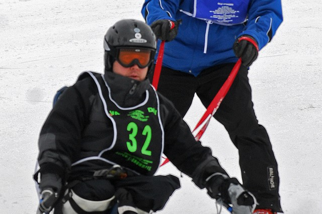"""Joey Bozik uses a bi-ski to go downhill during his fourth year at the National Disabled Veterans Winter Sports Clinic. In 2004, while serving in Iraq as a military police officer with the 82nd Airborne Division, he lost both legs and one arm from an IED blast. He can walk again thanks to two powered """"C-leg"""" prosthetics that have a computer chip in the knee, and he also has a prosthetic arm."""
