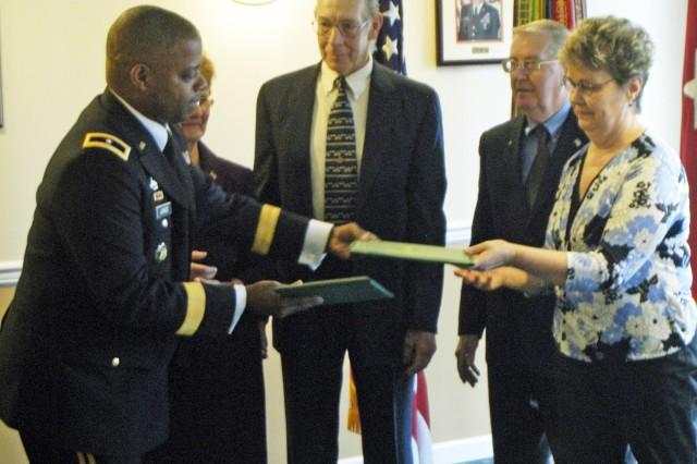Brig. Gen. Reuben Jones, Army adjutant general, hands the Distinguished Service Cross to the family members of Sgt. 1st Class William T. Miles, April 22, 58 years after he disappeared after parachuting into enemy territory.
