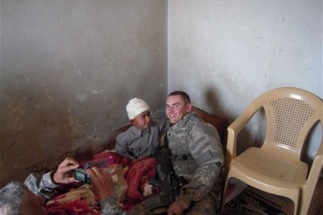 Spc. Michael Rankin, driver, Alpha Co., 1st Battalion, 184th Infantry Regiment, 30th Combat Sustainment Support Battalion, 16th Sustainment Brigade, visits the Iraqi boy that ran into a Coalition forces convoy and received minor injuries.