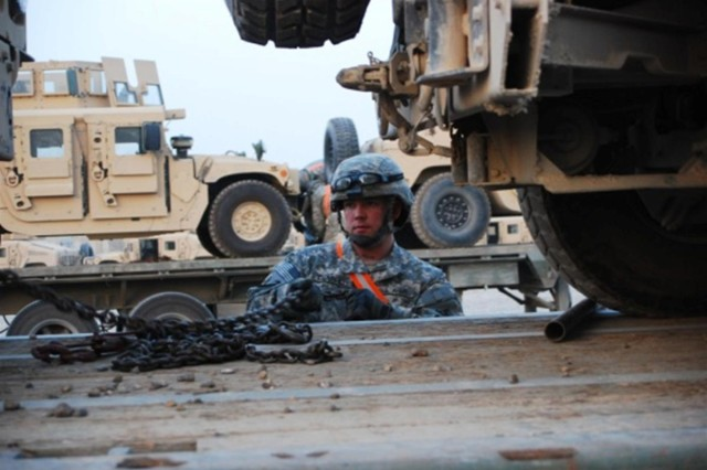 Sgt. Michael Chappell, a Salt Water, Okla. native, with the 68th Transportation Company, 419th Combat Sustainment Support Battalion, 10th Sustainment Brigade straps down a humvee on a M915/M872 tractor-trailer while transporting mission essential equipment throughout Iraq at Camp Taji, Iraq, in March.