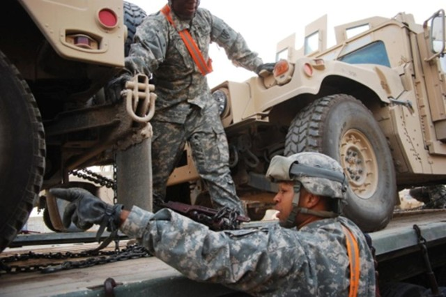 Staff Sgt. Karenthia T. Bland with the 68th Transportation Company inspects the tie-downs of a humvee on a M915/M872 tractor-trailer during a transportation mission at Camp Taji, Iraq in March.