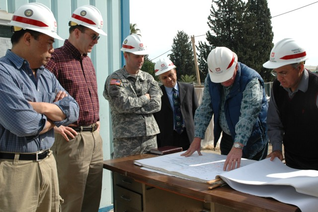 Charles Truesdell (second from right), a quality assurance representative with the Europe District Turkey Resident Office, shows Col. John Kem, Europe District commander, and other district staff construction documents for the $5.2 million Consolidated Communications Facility at Incirlik Air Base during a visit in February.