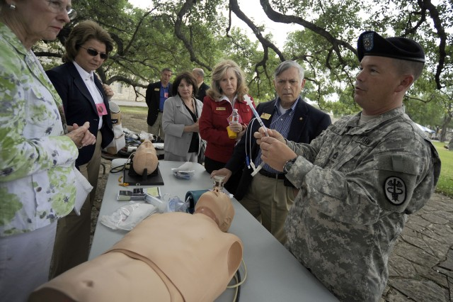 Sgt. 1st Class Blair Pilgrim, Emergency Medical Services NCOIC, demonstrates the use of standardized medical apparatus employed by the Army to several Civilian Aides to the Secretary of the Army during their visit to Fort Sam Houston in San Antonio, Texas, April 27.