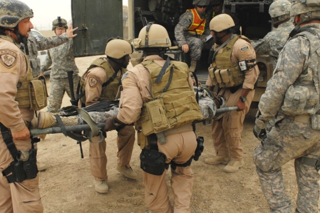 BAGHDAD - Members of a rapid response team load a wounded Soldier onto a field line ambulance from a nearby troop medical clinic on Victory Base Complex during a mass casualty training exercise held on Apr. 24. The exercise was designed to bring together the multiple civilian and military agencies that provide emergency services to everyone on VBC.