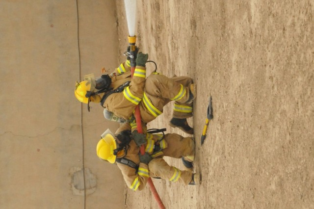 BAGHDAD - Two firefighters from the Camp Victory Fire Department extinguish a simulated fire caused by vehicle borne improvised explosive device during a mass casualty training exercise held on Victory Base Complex on Apr. 24. The training exercise simulated an attack at an entry control point that prompted responses from several agencies, both military and civilian, from across VBC.