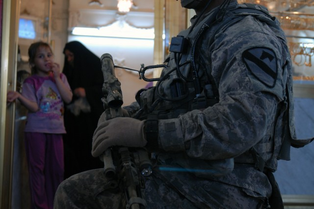 BAGHDAD - Wichita, Kan. native, Cpl. Anthony Jackson, a sniper with Headquarters and Headquarters Company, 2nd Battalion, 5th Cavalry Regiment, takes a knee in front of a gold shop at Ula Market in Sadr City, April 19. The patrol stopped here to assess the local butcher shops, which they plan to improve with a micro-grant.