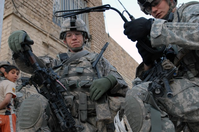BAGHDAD - Sgt. 1st Class Jason Peck (left), a platoon sergeant from Malone, N.Y., and 1st Lt. Robert Logisz from Chicago, assigned to Company C, 2nd Battalion, 5th Cavalry Regiment, patrol a neighborhood in Sadr City April 19.