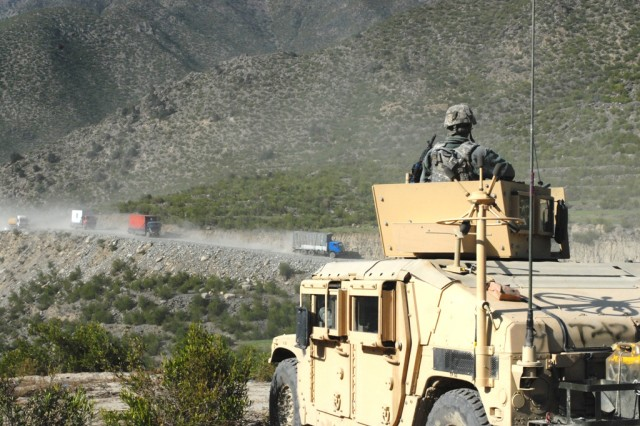 A Combat Logistics Patrol roves up an unpaved road as they receive security coverage from the scouts of Headquarters and Headquarters Troop, 6th Cavalry, 4th Regiment, 3rd Brigade Combat Team, 1st Infantry Division. The stretch of road is frequently attacked so the security is necessary to the overall mission success.