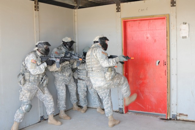 """Soldiers from the 524th Combat Sustainment Support Battalion kick down the door as they prepare to move into the shoot house at Pohakuloa Training Area April 14 on the big island of Hawaii.  The 524 CSSB is preparing for a deployment this summer."""""""
