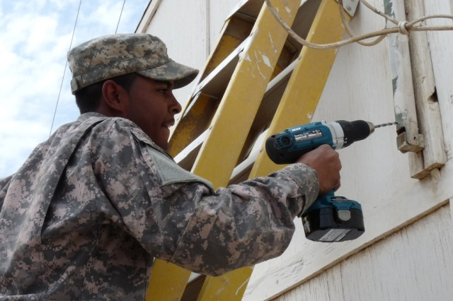 BAGHDAD - Over the course of his work day, Camden, S.C. native, Pvt. Brandon Sharper, a communications specialist with the 46th Engineer Combat Battalion, 225th Eng. Brigade, operates a power drill while running communications lines on Camp Liberty.