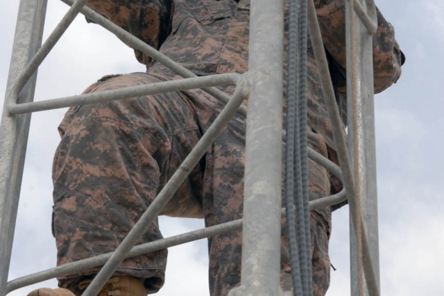 BAGHDAD - Brewster, N.Y. native, Pvt. Michael Slocum, raid camera operator for the base defense operating cell (BDOC), 115th Brigade Support Battalion, 1st Brigade Combat Team, 1st Cavalry Division climbs a tower to release the brakes that allow the tower to descend to its resting position April 26 on Joint Security Station War Eagle, north of Baghdad.  The BDOC cleans the raid tower to ensure optimum performance.