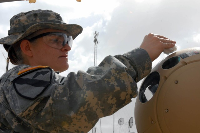 BAGHDAD - Irving, Texas native, Sgt. Malinda Fox, noncommissioned officer in charge for the badging cell, 115th Brigade Support Battalion, 1st Brigade Combat Team, 1st Cavalry Division wipes the camera lenses off during a routine raid tower cleaning April 26 on Joint Security Station War Eagle, north of Baghdad.