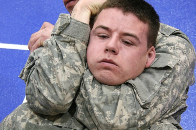 "Sgt. Brandon Amarone applies a choke hold to Pfc. Joshua Corey, both Military Police Officers, 49th Missile Defense Bn., during the 2009 Fort Greely ""AC"" Best Warrior Competition. Amarone went on to win the title of the 49th Missile Defense Bn. ""AC"" NCO of the Year."