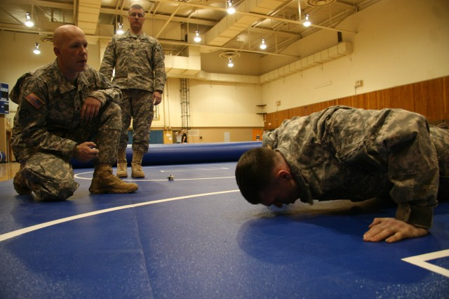 """Spc. James Bates (far left), counts the repetitions of Spc. James Kempner (pushing),   both Military Police Officers, 49th Missile Defense Bn.,  during the 2009 Fort Greely """"AC"""" Best Warrior Competition  as the battalion's top enlisted leader, Command Sgt. Maj. Bradford Quigley observes the push-up event."""