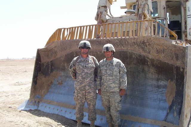 """BAGHDAD - Six foot, two inch Ventress, La. Native, Command Sgt. Maj. Joe Major (left,) from the 225th Engineer Brigade, stands in front of the 14-foot wide blade attached to the military D-9 Bulldozer with Pfc. Eric Salinas (right), a member of the 46th Eng. Combat Battalion (Heavy), 225th Eng. Bde., 1st Cavalry Division. Salinas, from Victoria, Texas, showed Major how to operate the large piece of machinery while clearing debris around Sather Airbase on Victory Base Complex April 27.  """"I have driven a lot of dozers in my time,"""" said Major who has more than 30-years in the National Guard. """"Like the D-7 and D-8, but nothing as big as the D-9. It was an experience."""""""