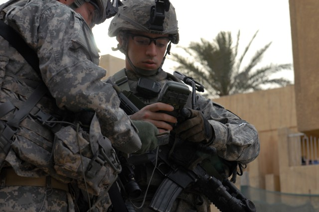 BAGHDAD -Pvt. Daniel Owen (left) and Cpl. Justin Hebert of Company B, 2nd Battalion, 5th Cavalry Regiment, input coordinates onto a digital advanced GPS receiver in Sadr City, April 26.